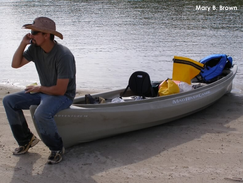 Joel Jorgensen on the phone on a canoe on a river sandbar